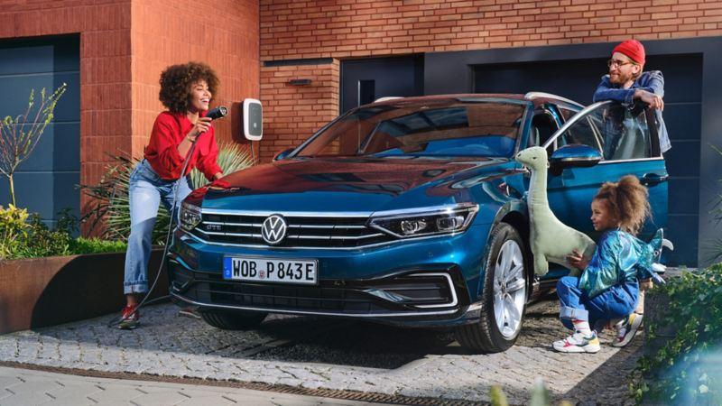 Una famiglia gioca attorno a una Volkswagen Passat GTE, vista frontalmente, parcheggiata fuori da una casa.