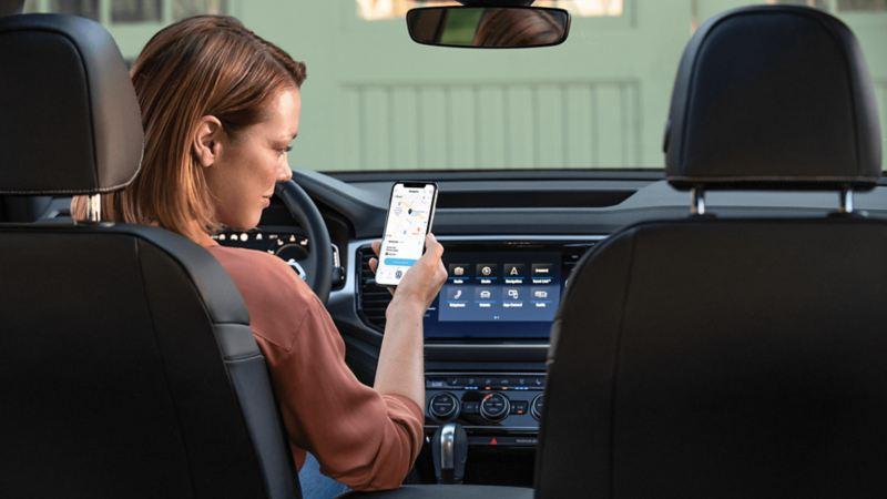Une femme assise dans un véhicule Volkswagen regardant l'application Car-NetMD