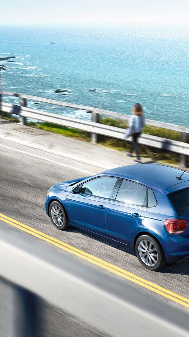 Μπλε Volkswagen Polo TGI κινείται σε γέφυρα κοντά στη θάλασσα.