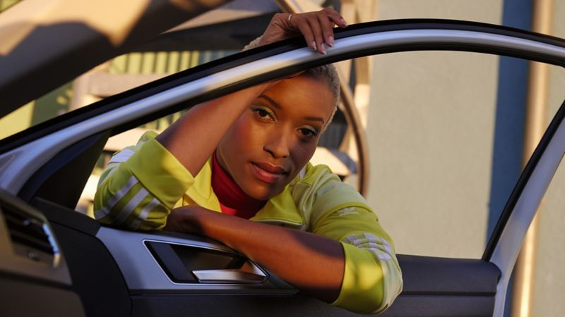 Polo VW blanc ACTIVE. Vue d'une femme de l'intérieur à travers une porte et une fenêtre ouvertes.