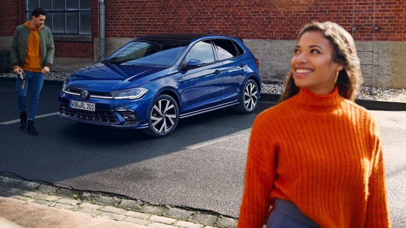 VW Polo in blau, Front- und Seitenansicht, Junge Frau und junger Mann gehen an Fahrzeug vorbei