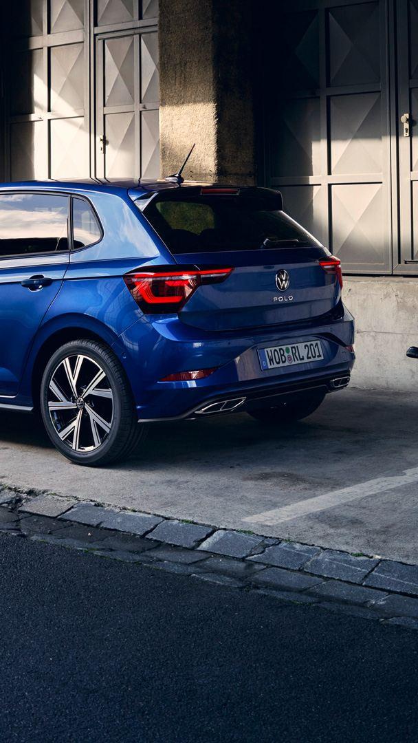 Blå VW Polo står foran en rampe, en mann går forbi bakparten, som har LED-baklykter