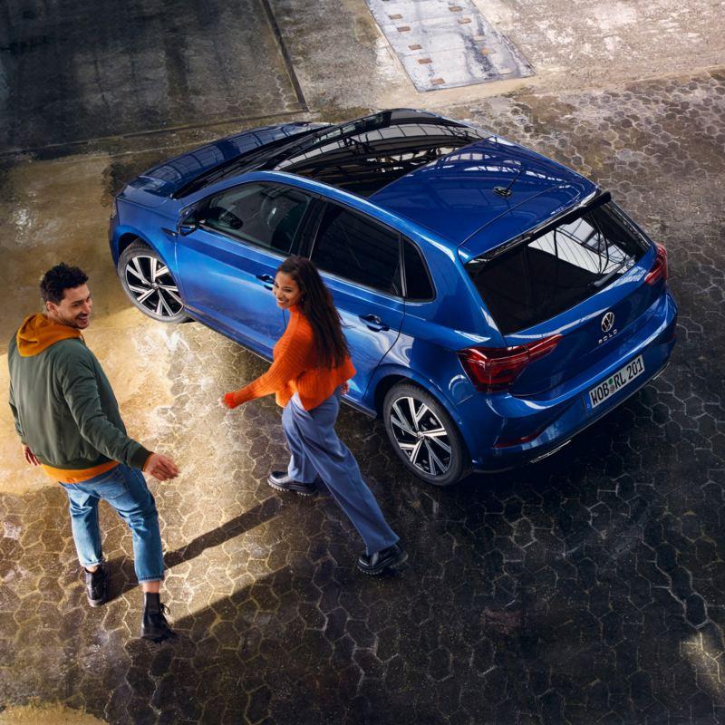 Una coppia di ragazzi si avvicina a Volkswagen Nuova Polo, vista 3/4 posteriormente, parcheggiata in garage.