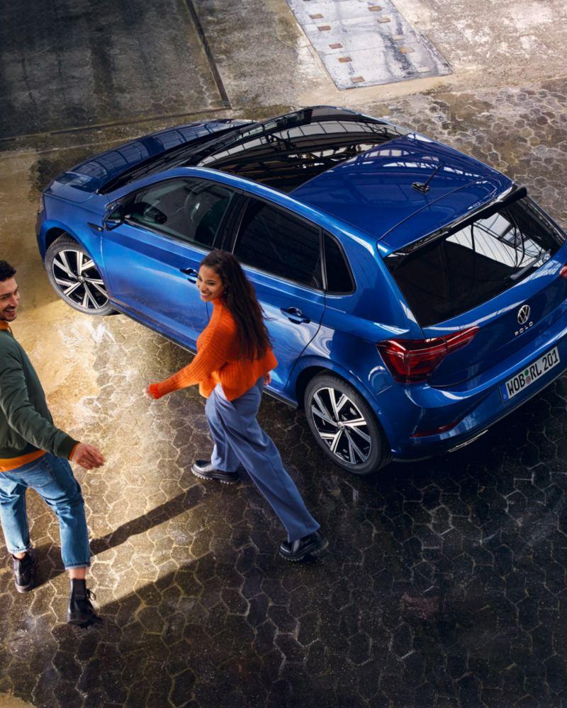 Due ragazzi si avvicinano a Volkswagen Nuova Polo, vista 3/4 posteriormente dall'alto, con tetto panoramico scorrevole chiuso.