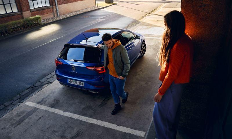 Une Polo bleue aux vitres arrière teintées est garée devant une rampe. Une femme est assise sur la rampe, un homme s'en approche.
