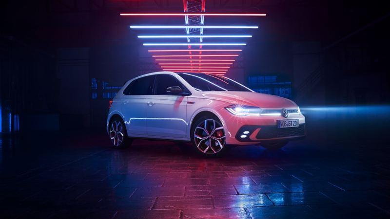 Scatto di una VW Polo GTI bianca in un capannone buio con le luci LED accese sotto elementi luminosi.