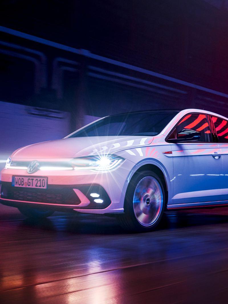 Une VW Polo GTI blanche roule dans une halle avec des phares matriciels à LED allumés et une barre lumineuse à l'avant.