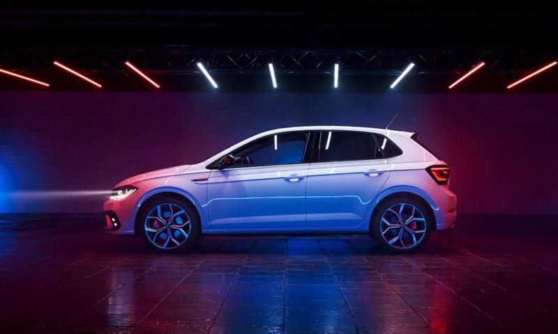Vue de côté d'une VW Polo GTI blanche avec vitres arrière teintées, emblème GTI sur l'aile et jantes de 18 pouces «Faro» en option.