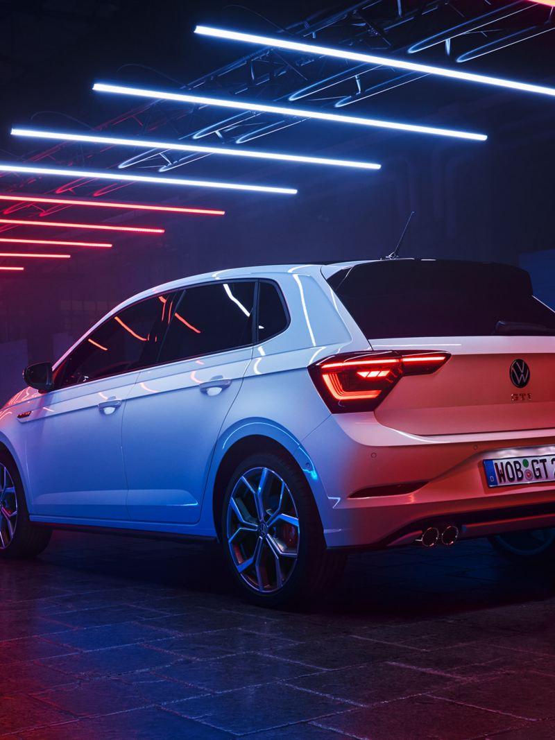 Blick von hinten au einen weißen Polo GTI, welcher mit eingeschalteten LED-Heckleuchten in einer dunklen Halle unter Leuchtelementen steht.