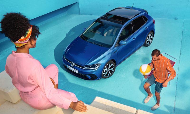 Un polo bleu se trouve dans une piscine vide, vue d'en haut sur le côté et le toit panoramique inclinable / coulissant ouvert. Un homme joue au ballon, une femme est assise au bord de la piscine.