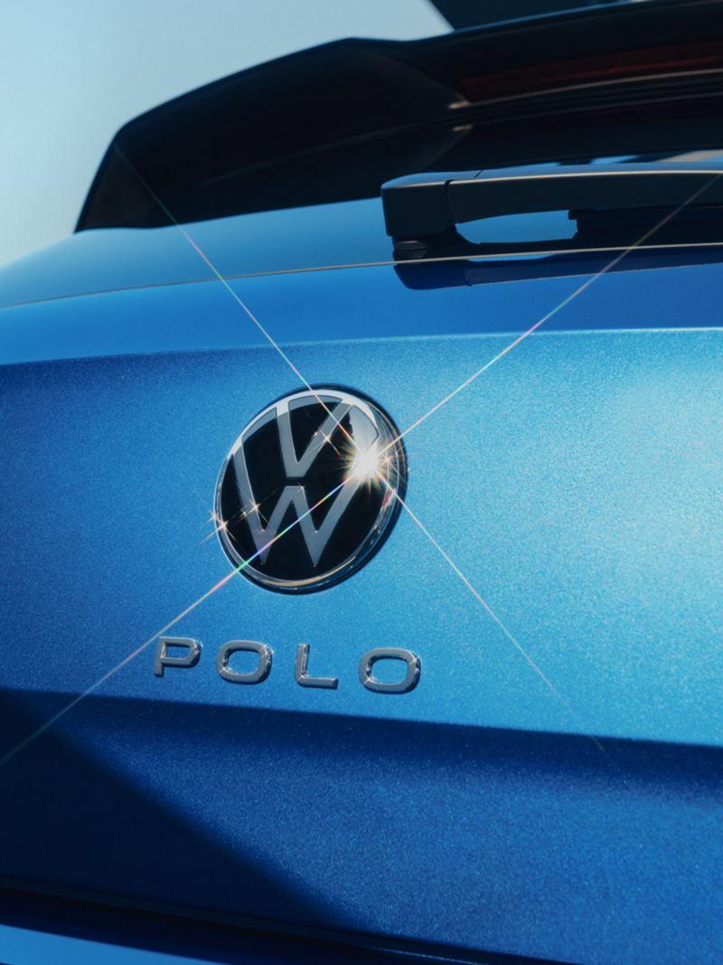 Vue détaillée du logo de Volkswagen et du lettrage « Polo » sur le hayon de la Polo bleue.