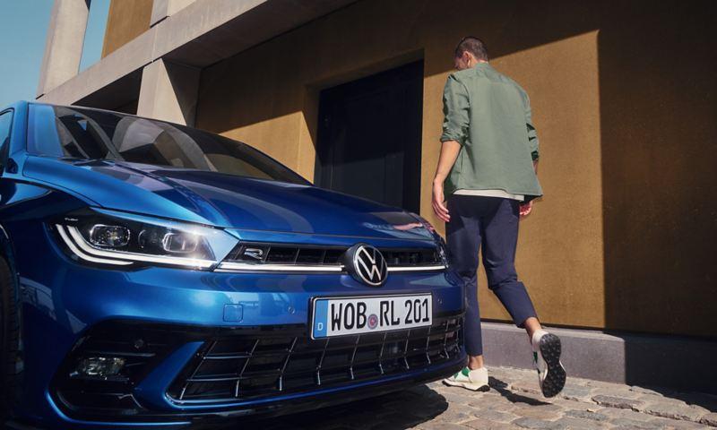 Vue détaillée de l'avant avec les phares matriciels à LED IQ.LIGHT de la VW Polo bleue, un homme passe devant eux sur le côté.