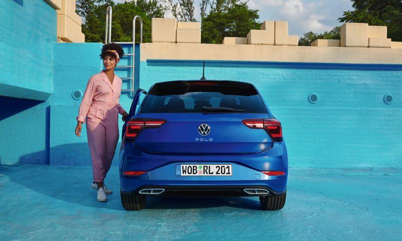 Vue de l'arrière d'une VW Polo bleue, garée dans une piscine vide. Une femme en salopette rose ouvre la portière du conducteur.