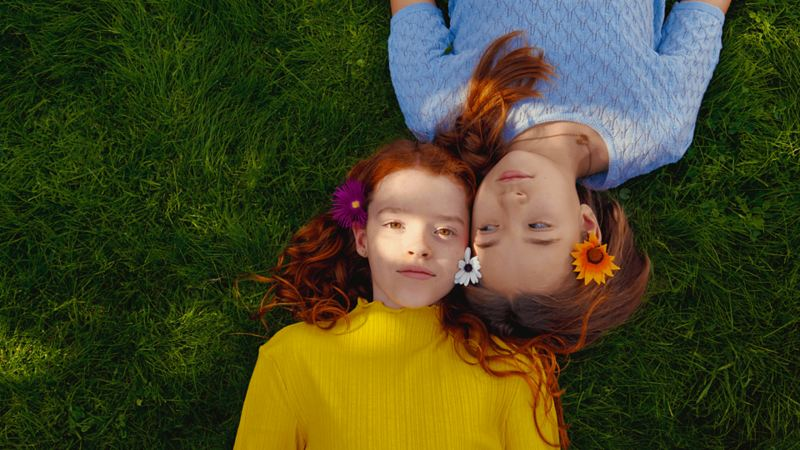 Two kids laying down on grass