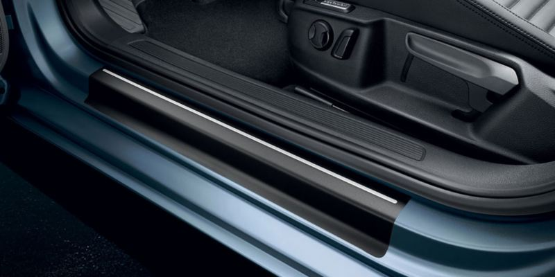 Dettaglio delle pellicole battitacco nere con strisce argento originali Volkswagen, applicate su una Passat.