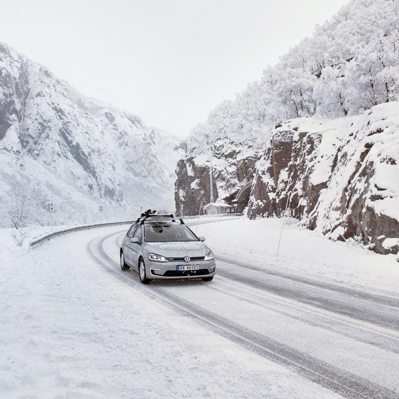Une Volkswagen est équipée de roues complètes hiver roule sur une route enneigée