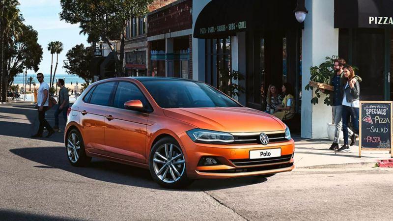 Vista 3/4 frontale di Volkswagen Polo parcheggiata davanti ad un negozio.