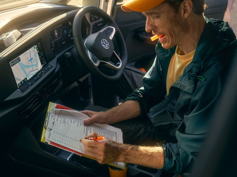 Courier writing on clipboard inside Volkswagen Caddy Cargo.