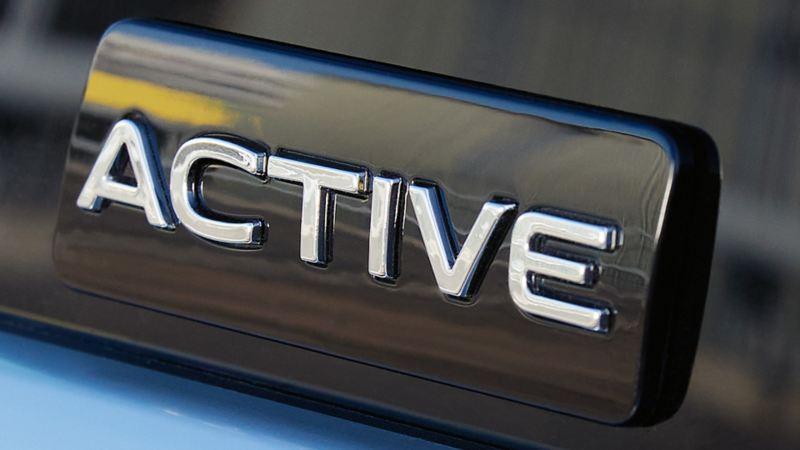 Plakietka modelu VW ACTIVE na drzwiach białego VW ACTIVE.