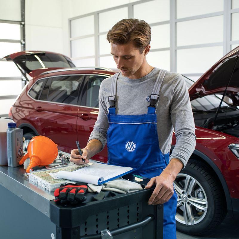 VW-servicemedewerker voor een rode Volkswagen met dieselmotor en met open motorkap in een werkplaats