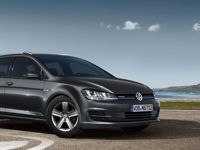 A grey VW Golf TGI Variant BlueMotion on a parking space next to the sea