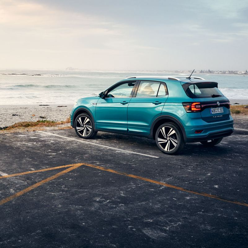 A turquoise VW T-Roc with all-season wheels on a parking place with view on the sea