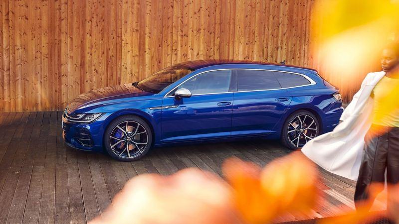 Una Volkswagen Arteon R Shooting Brake di colore blu parcheggiata davanti a una parete di legno