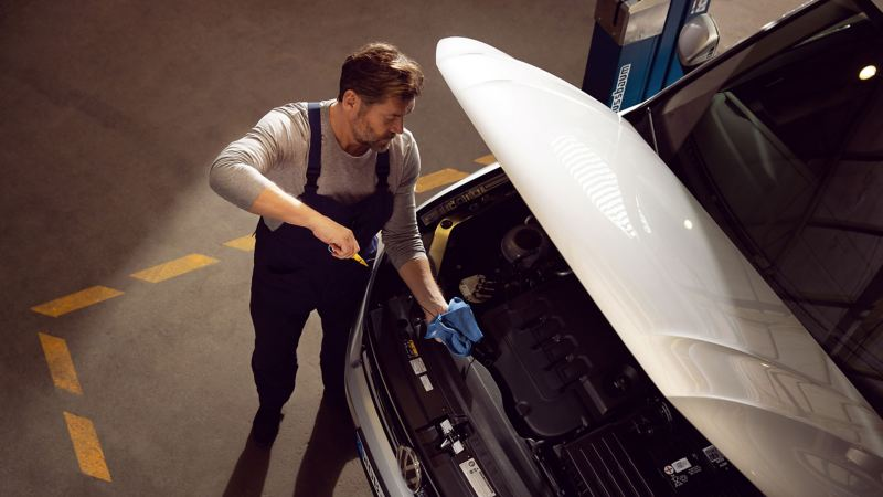 A VW service employee is checking the oil level of a VW car