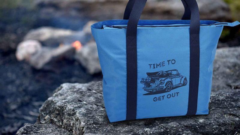 """Borsa da spiaggia blu della collezione Heritage di Volkswagen, appoggiata su uno scoglio, con il disegno di un Maggiolino e la scritta """"Time to get out""""."""