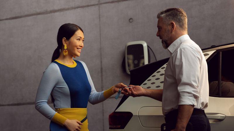 Un'impiegata Volkswagen porge a un cliente le chiavi della sua Volkswagen ID.