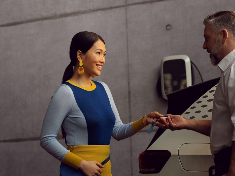 Un addetto all'assistenza VW consegna a un cliente le chiavi della sua VW ID.3