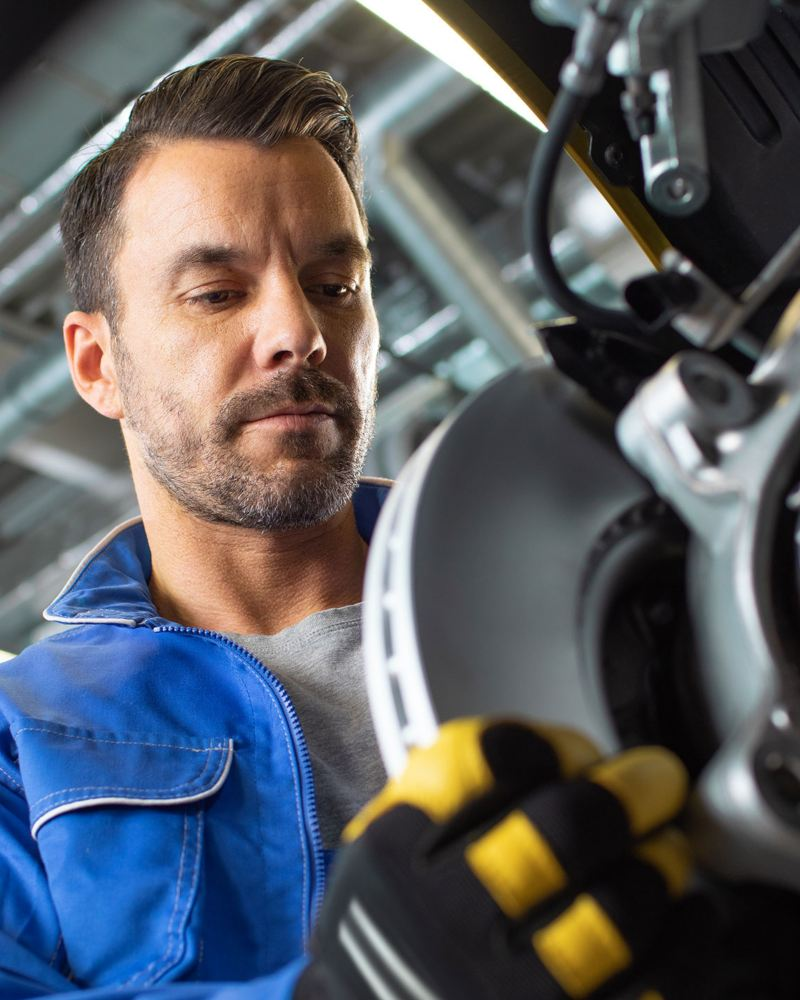 VW service employee replaces a brake disc: our Volkswagen Genuine Parts®