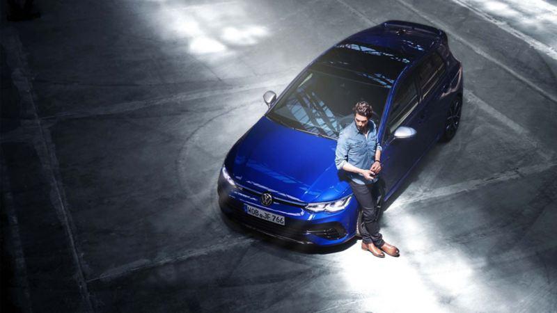 Inquadratura dall'alto di un uomo appoggiato al cofano della sua auto Volkswagen, vista 3/4 frontalmente.