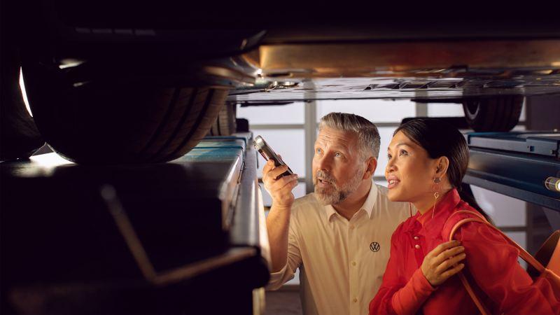 En VW servicemedarbejder viser en kunde noget på hendes elbil – VW service på elbiler