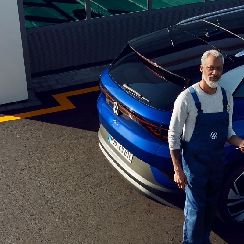 A Volkswagen service mechanic stands in front of a blue ID.4 outside a workshop