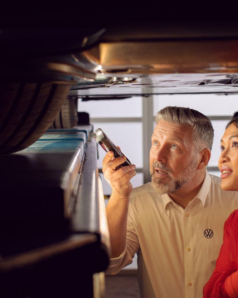 Ein VW Servicemitarbeiter zeigt einer Kundin etwas an ihrem Elektroauto – VW Service für elektrische Fahrzeuge
