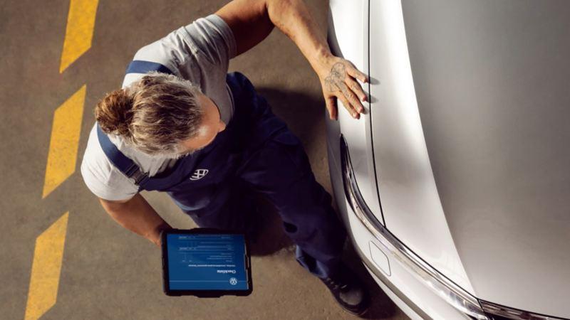 Un technicien Volkswagen Service contrôle un véhicule  en atelier.