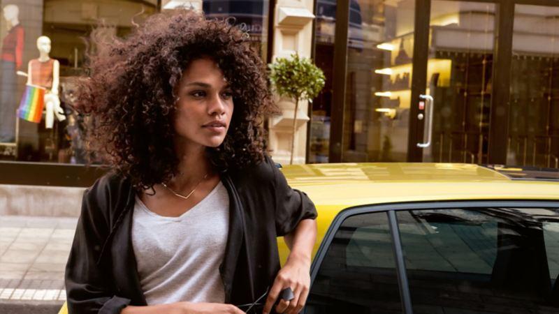 Una mujer se apoya en su coche Volkswagen. Modelos antiguos de Volkswagen