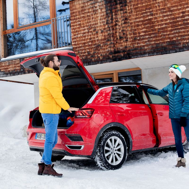 A man and a woman stand by their red VW T-Roc with vw winter tyres in winter