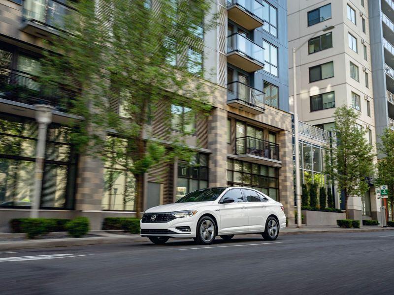 Une Jetta blanche est conduite dans une rue de la ville bordée d'arbres. lien vers offers.vwmodels.ca