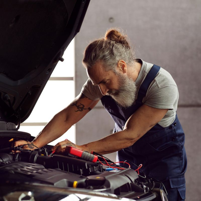 Technicien Volkswagen Véhicules Utilitaires en train de vérifier une batterie