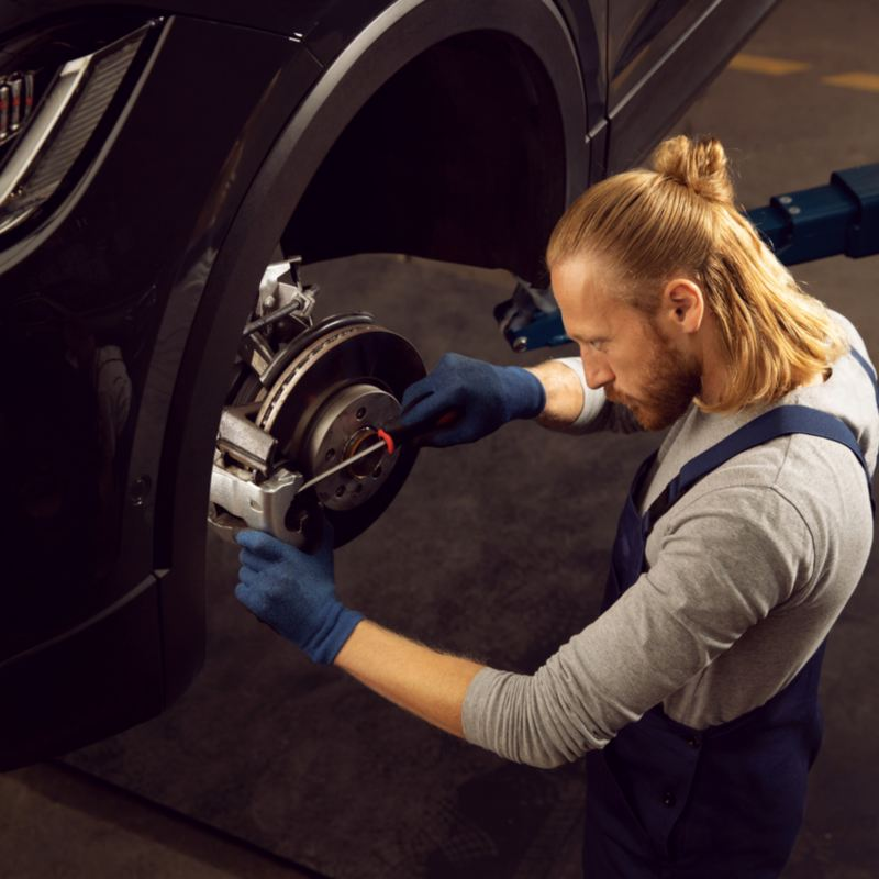 A VW employee changes the Volkswagen Brakes on a VW in a VW workshop