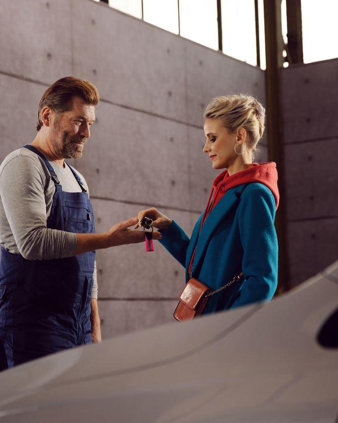 un technicien dans un atelier de réparation volkswagen remet les clés de voiture à une cliente