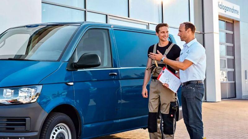 Uno specialista Volkswagen e un cliente discutono dei piani di manutenzione Service Plan per Veicoli Commerciali accanto a un Transporter  Furgone.