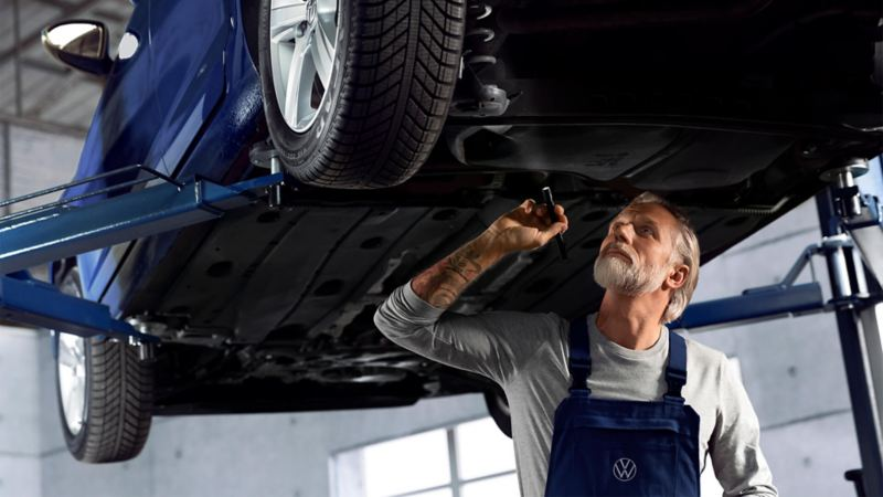 man looking under the car at shock absorbers