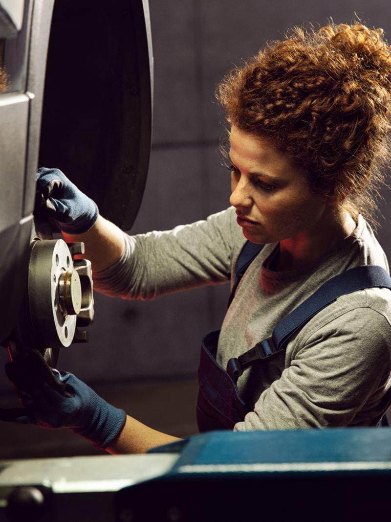 Un employé d'entretien VW lors d'une vérification des freins, lien vers la page des pièces VW