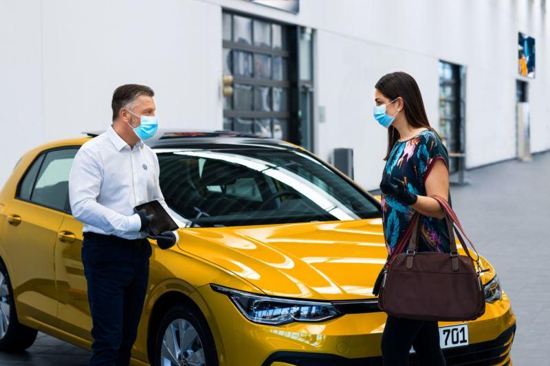 Agente oficial de Volkswagen atendiendo a una clienta junto a un Golf 8 amarillo en la puerta de un concesionario