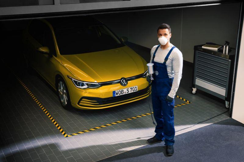 Mecánico de Volkswagen con una pistola de pintura frente a un Golf 8 amarillo en el taller