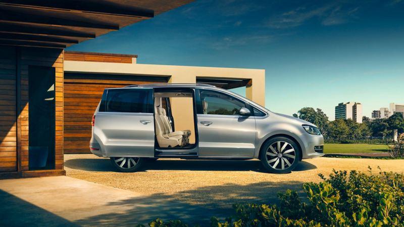 Vista laterale di Volkswagen Sharan parcheggiata davanti a un ingresso.