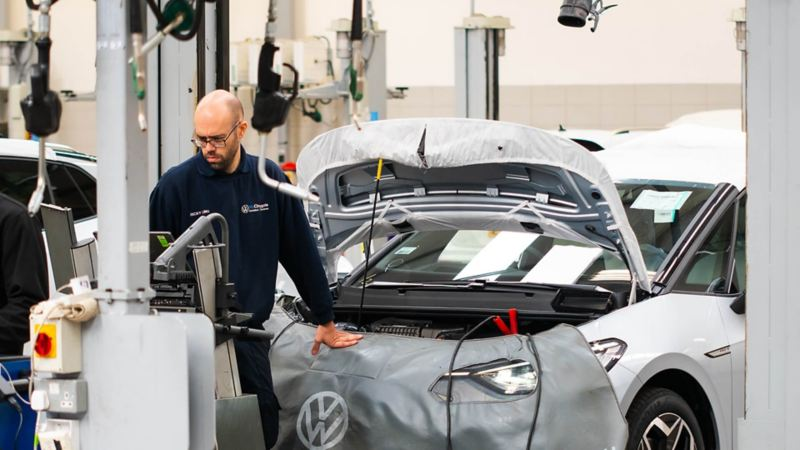 A technician working standing in front of a VW with the bonnet raised